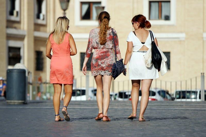 Drei gehende und sprechende Freunde stockbild