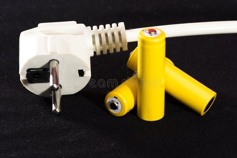 Drei gelbe Batterien und Ladegerät verstopfen Nahaufnahme auf einem unscharfen Hintergrund des dunklen Schwarzen elektrik Batteri lizenzfreies stockbild