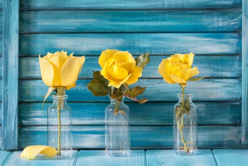 Drei gelbe Rosen auf einem Hintergrund des Blaus malten Bretter lizenzfreies stockbild