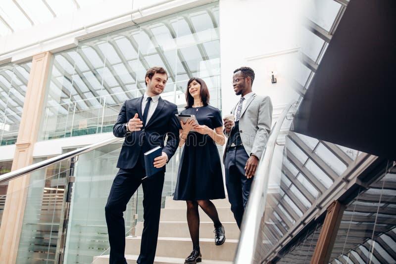 Drei gemischtrassige Geschäftsleute, die unten auf Treppe mit digitaler Tablette gehen lizenzfreie stockfotografie
