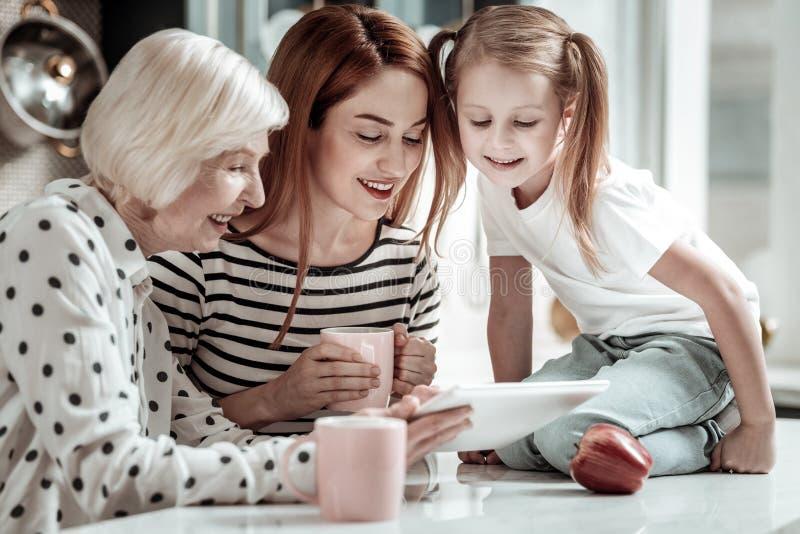 Drei Generationen, die den Schirm der modernen Tablette lächeln und betrachten stockbilder