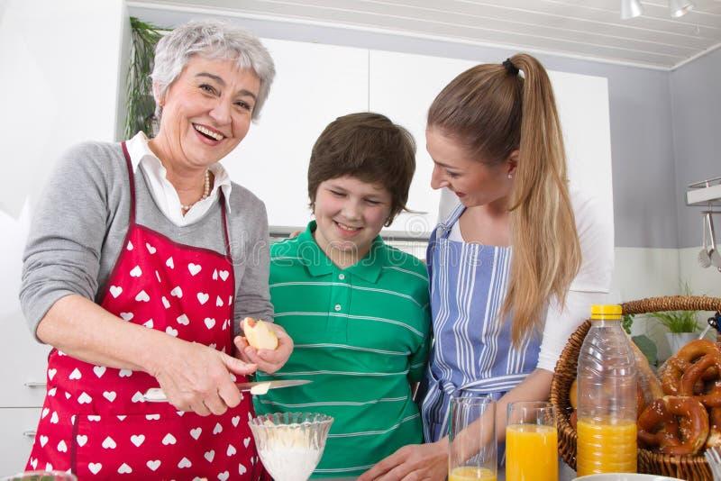 Drei Generationen, die zusammen - glückliche Familie kocht togethe leben lizenzfreie stockfotos