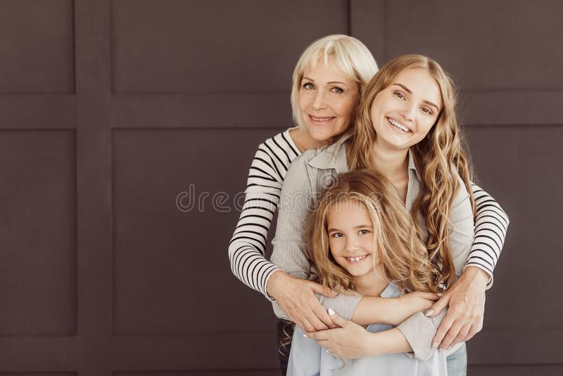 Drei Generationen von den glücklichen Frauen, die Kamera betrachten stockbild