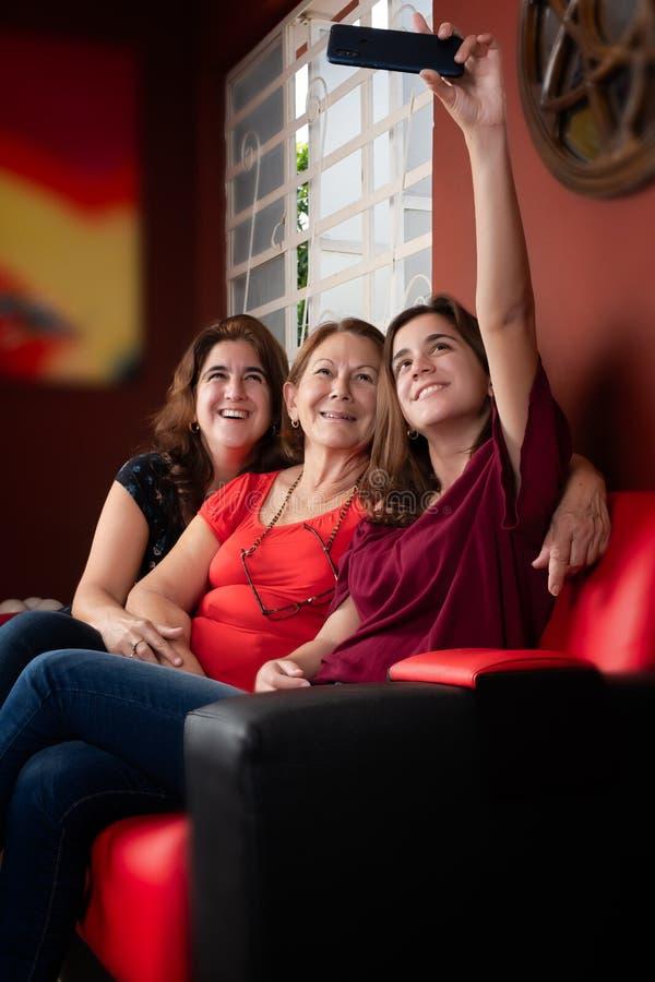 Drei Generationen von den hispanischen Frauen, die ein selfie nehmen stockbilder