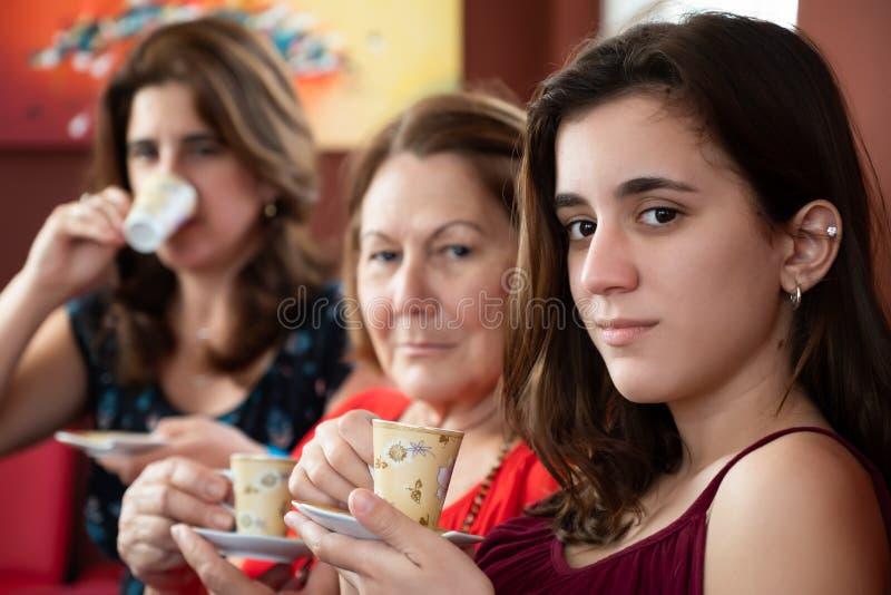 Drei Generationen von den hispanischen Frauen, die Kaffee trinken lizenzfreie stockfotografie
