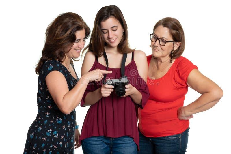Drei Generationen von den hispanischen Frauen, die photpgraphs auf einer Digitalkamera betrachten stockfotografie