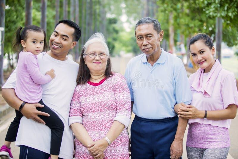 Drei Generationsfamilienblicke an der Kamera lächeln stockfotos