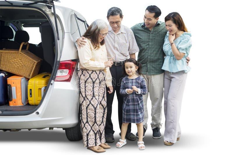 Drei Generationsfamilienstände nahe ihrem Auto stockbilder