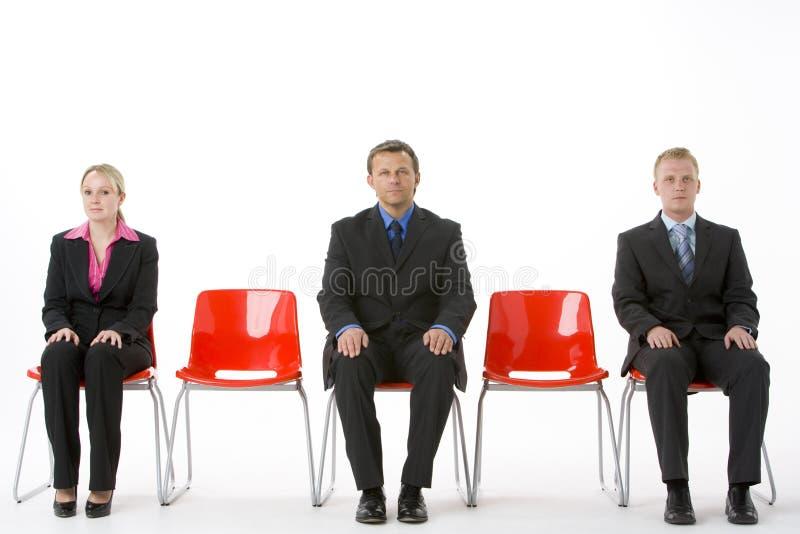 Drei Geschäftsleute, die auf roten Plastiksitzen sitzen stockbilder