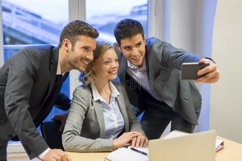 Drei Geschäftsleute, die ein Selfie im Büro machen lizenzfreie stockfotos