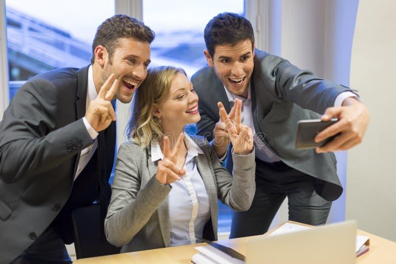 Drei Geschäftsleute tun ein glückliches Selfie im Büro stockfotos