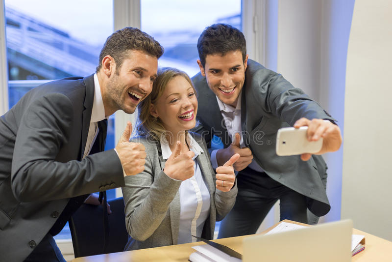 Drei Geschäftsleute tun ein glückliches Selfie im Büro Der Daumen lizenzfreies stockbild