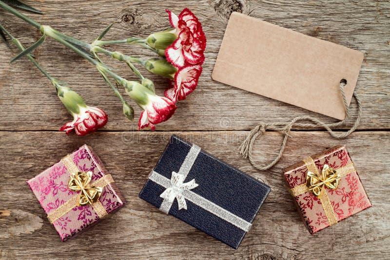 Drei Geschenkboxen, Gartennelke und leeres Tag lizenzfreie stockbilder