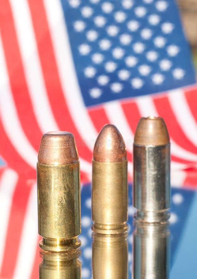 Drei Gewehrkugeln auf US-Markierungsfahnenhintergrund stockbilder