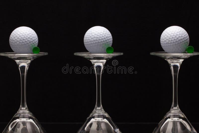Drei Gläser Champagner und weiße Golfbälle stockfotos