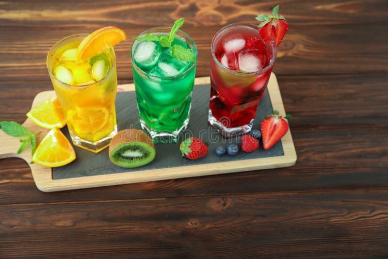 Drei Gläser verschiedene kalte Sommergetränke oder Auffrischungscocktails färben sich gelb, grünen, rot in den giftigen Farben lizenzfreie stockfotografie