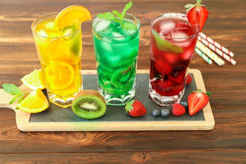 Drei Gläser verschiedene kalte Sommergetränke oder Auffrischungscocktails färben sich gelb, grünen, rot in den giftigen Farben lizenzfreies stockbild