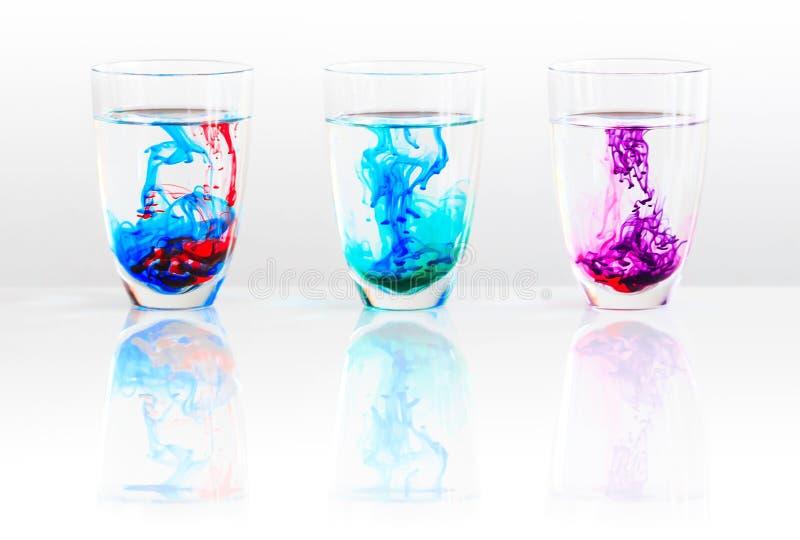 Drei Gläser Wasser und farbige Tinte lizenzfreie stockfotografie