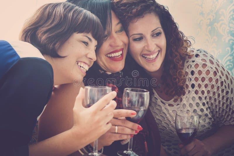 Drei glücklich und die schönen Fraufreunde haben Spaß etwas Rotwein zusammen zu Hause trinkend und die Freizeit und die Bindung g lizenzfreie stockbilder