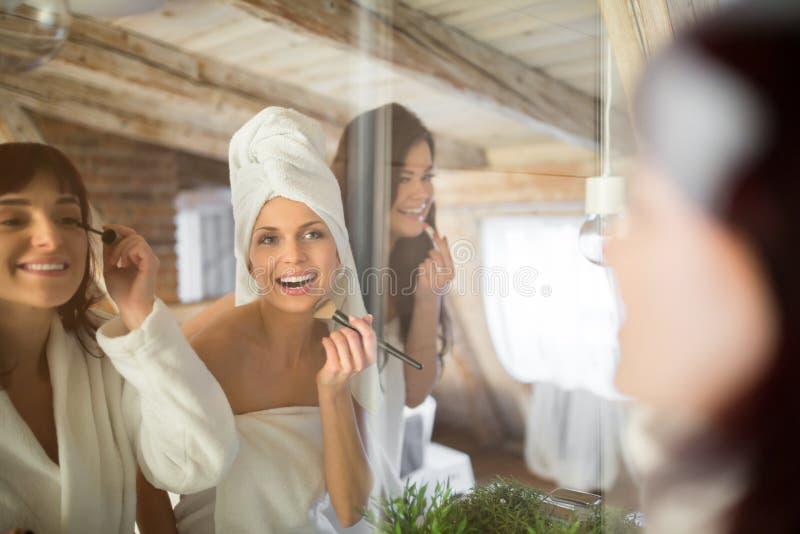 Drei glückliche Frauen, die sich reflektieren, beim Spiegelhandeln bilden lizenzfreies stockbild