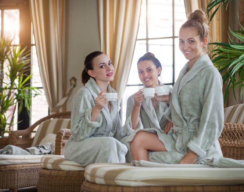 Drei glückliche Frauen, die Tee am Kurort trinken stockbild
