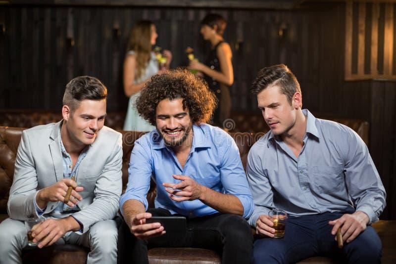 Drei glückliche Freunde, die Handy beim Essen der Zigarre und des Whiskys betrachten stockfotografie