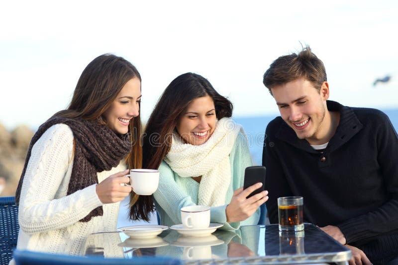 Drei glückliche Freunde, die Medien in einem Telefon in einer Stange aufpassen stockfotos