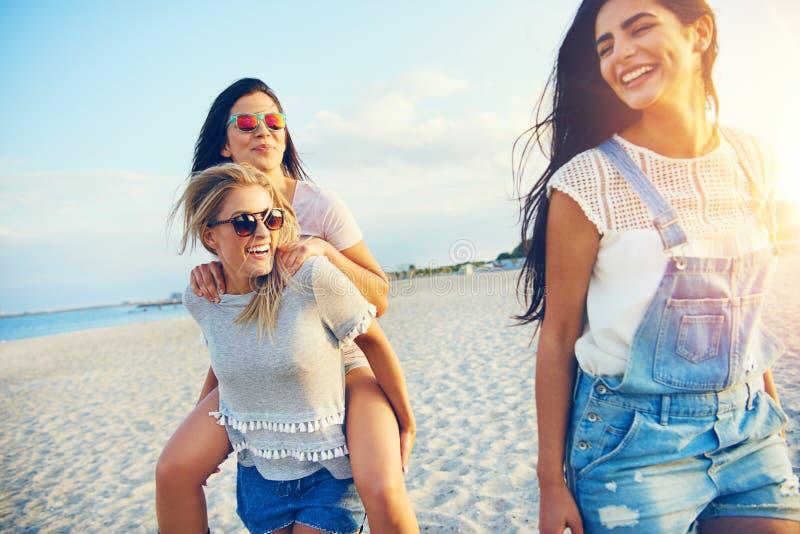 Drei glückliche Freundinnen, die auf Strand gehen stockfotografie