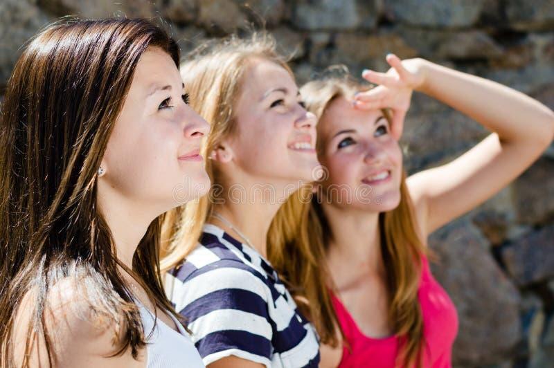 Drei glückliche jugendlich Freundinnen, die zusammen in einer Richtung schauen lizenzfreie stockfotografie