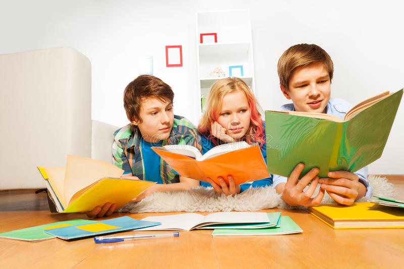 Drei glückliche jugendlich Kinder lasen die Bücher, die Hausarbeit tun lizenzfreie stockbilder