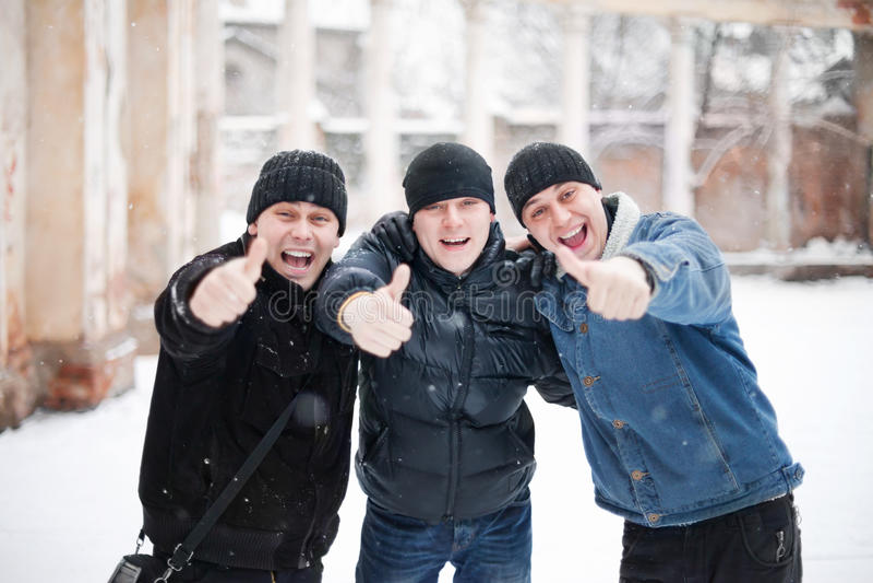 Drei glückliche junge Männer, die sich Daumen zeigen stockbild