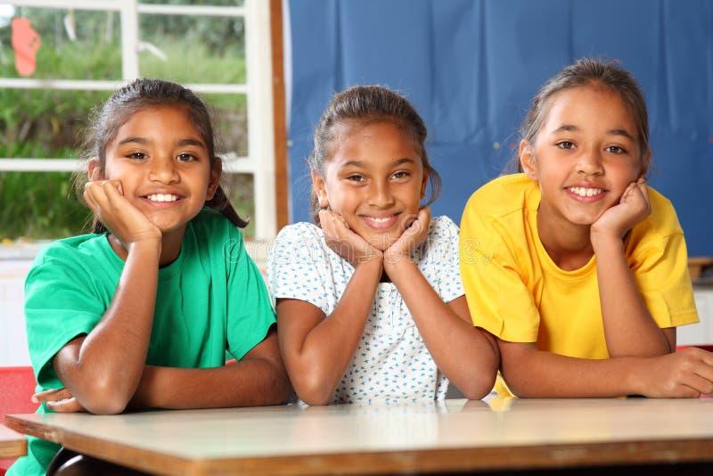 Drei glückliche junge Schulemädchen, die sich innen auf Schreibtisch lehnen lizenzfreie stockfotografie
