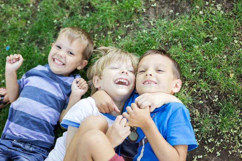Drei glückliche Jungen, die sich auf Gras im Sommerpark hinlegen lizenzfreies stockfoto