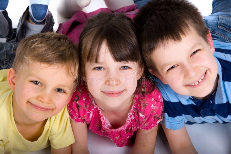 Drei glückliche Kinder auf dem Fußboden lizenzfreie stockfotos