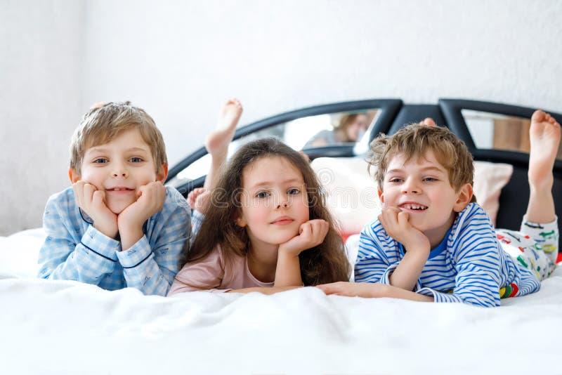 Drei glückliche Kinder in den Pyjamas Pyjamapartei feiernd Vorschule und Schuljungen und -mädchen, die Spaß zusammen haben lizenzfreies stockbild