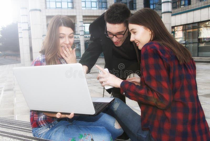 Drei glückliche lächelnde Highschool Jugendlichstudenten mit Laptop a stockbilder