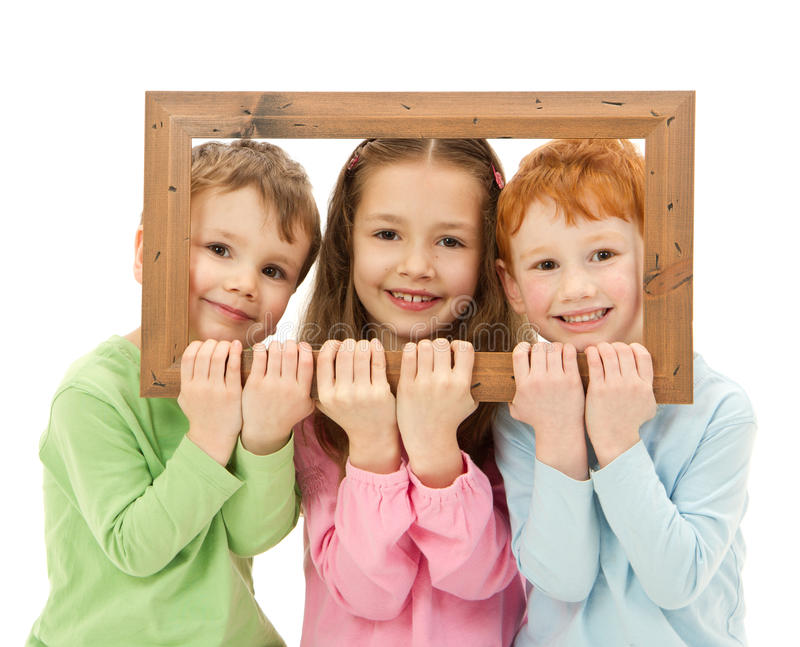 Drei glückliche lächelnde Kinder, die Bilderrahmen schauen stockfotos