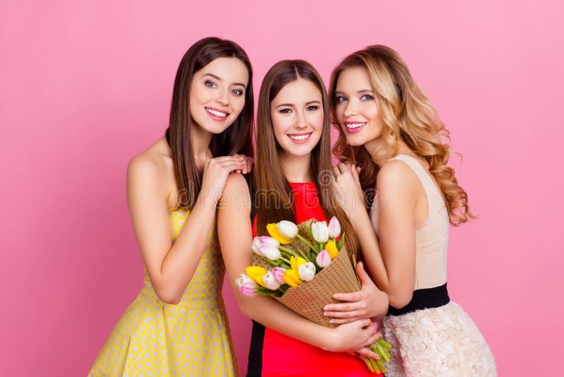 Drei glückliche schöne Mädchen zusammen in den eleganten Kleidern mit hai stockfoto
