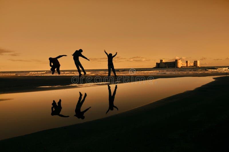 Drei glückliche springende Jungen stockfotos