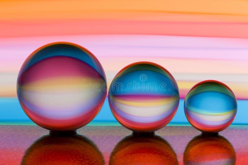 Drei Glasglaskugeln in Folge mit einem Regenbogen der bunten hellen Malerei hinter ihnen lizenzfreies stockfoto