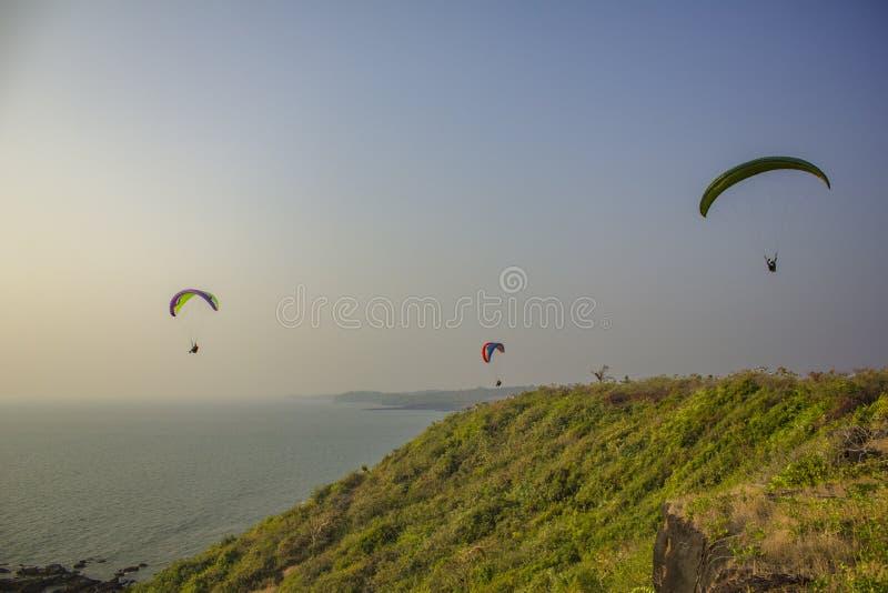 Drei Gleitschirme auf bunten Fallschirmen fliegen über das Meer und den grünen Hügel gegen einen sauberen blauen Himmel stockfotos