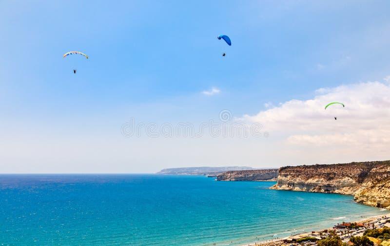 Drei Gleitschirme fliegend über den Kurions-Strand und Mittelmeer stockfotos