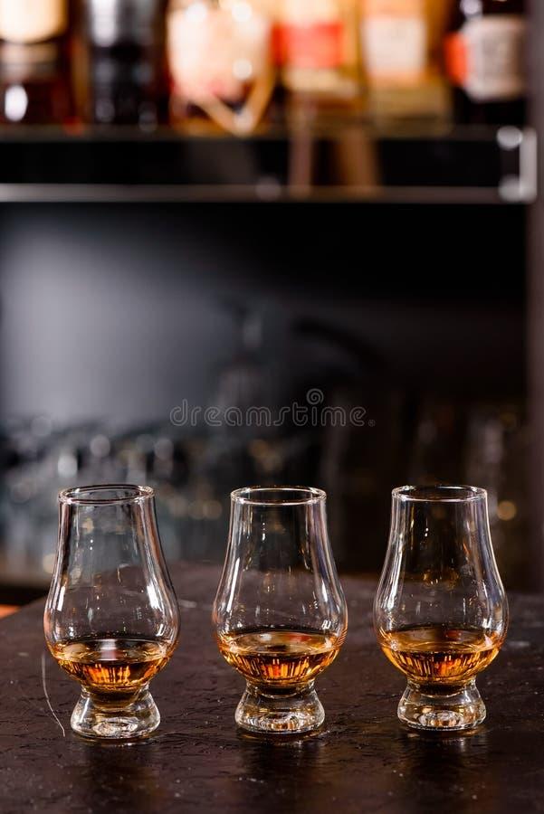 Drei Glencairn-Glas mit Whisky auf einem Stangenhölzernen Gegenabschluß oben auf dem Hintergrund von undeutlichen Flaschen stockbilder