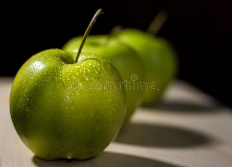 Drei grüne Äpfel in einer diagonalen Linie lizenzfreie stockfotografie