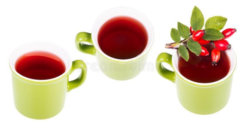 Drei grüne Becher mit heißem medizinischem Tee von den Hagebutten lizenzfreie stockbilder