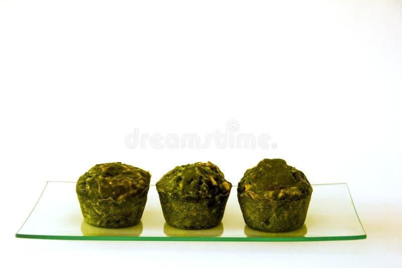 Drei grüne kleine Kuchen auf einem Glasbehälter stockfotos