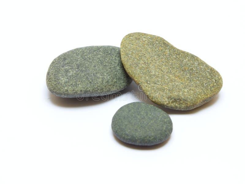 Drei graue Steine auf weißem Hintergrund stockfotos