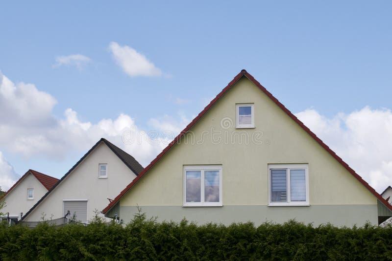Drei Häuser mit geworfenen Dächern lizenzfreies stockbild