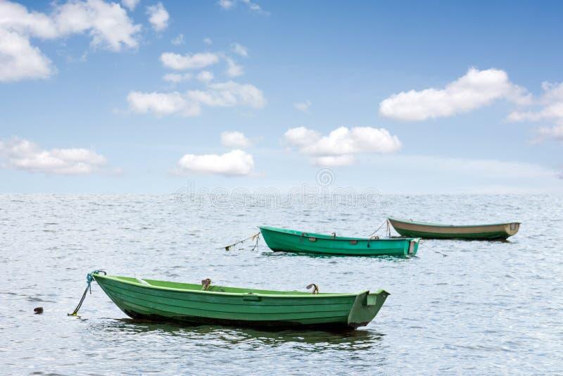 Drei hölzerne Boote in Meer stockfotografie
