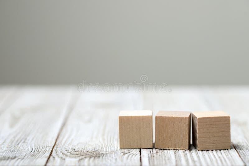Drei hölzerne Spielzeugwürfel auf grauem hölzernem Hintergrund lizenzfreie stockfotografie